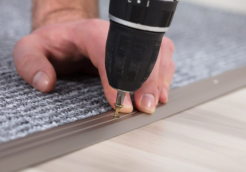 professional carpet worker working on carpet seam repair